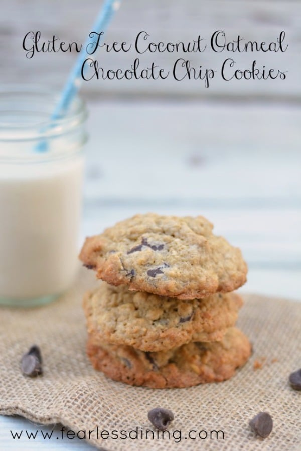 Easy Gluten Free Coconut Oatmeal Chocolate Chip Cookies stacked on top of each other. Chocolate chips are on the napkin. A glass of milk is in the background