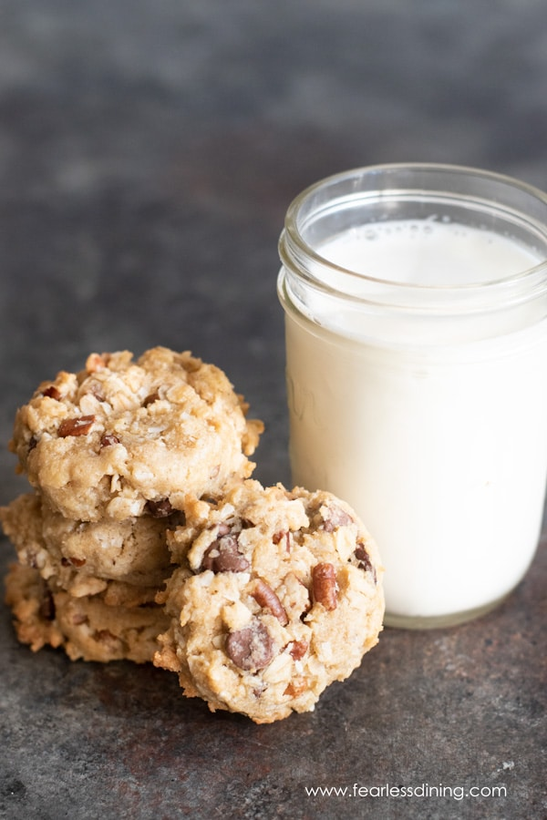 a stack of gluten free cowboy cookies next to a glass of milk