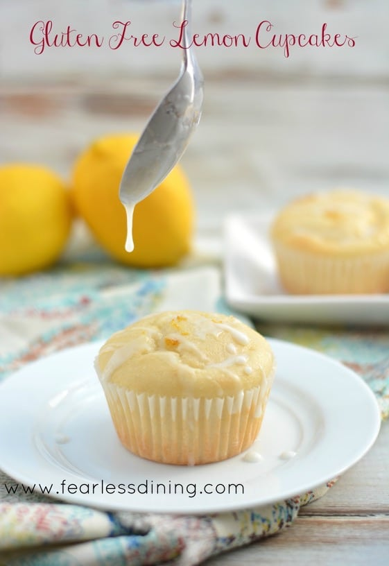 Gluten Free Lemon Cupcake on a plate with a spoon drizzling icing over the top.