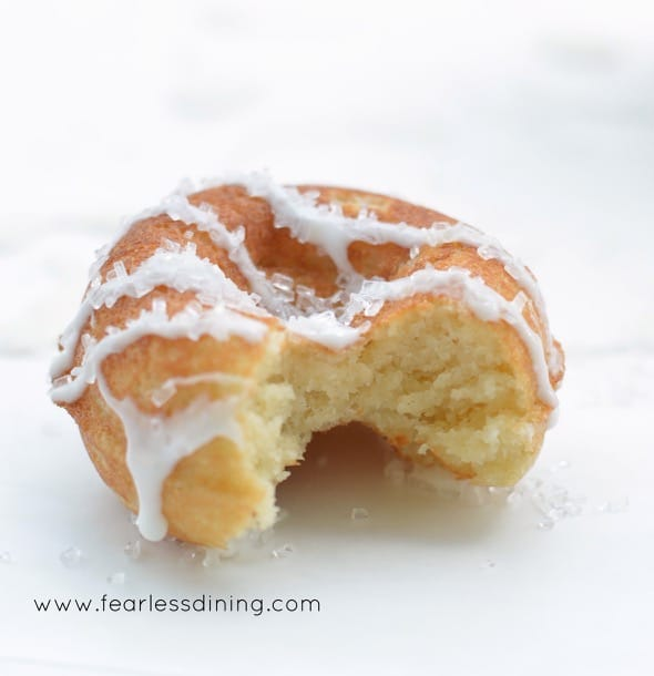 A single Gluten Free Lemon Donut with a bite taken out so you can see how light and fluffy the inside is.