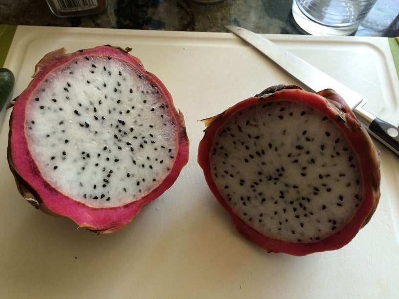 sliced open dragon fruit so you can see the hot pink rim and polka dot inside