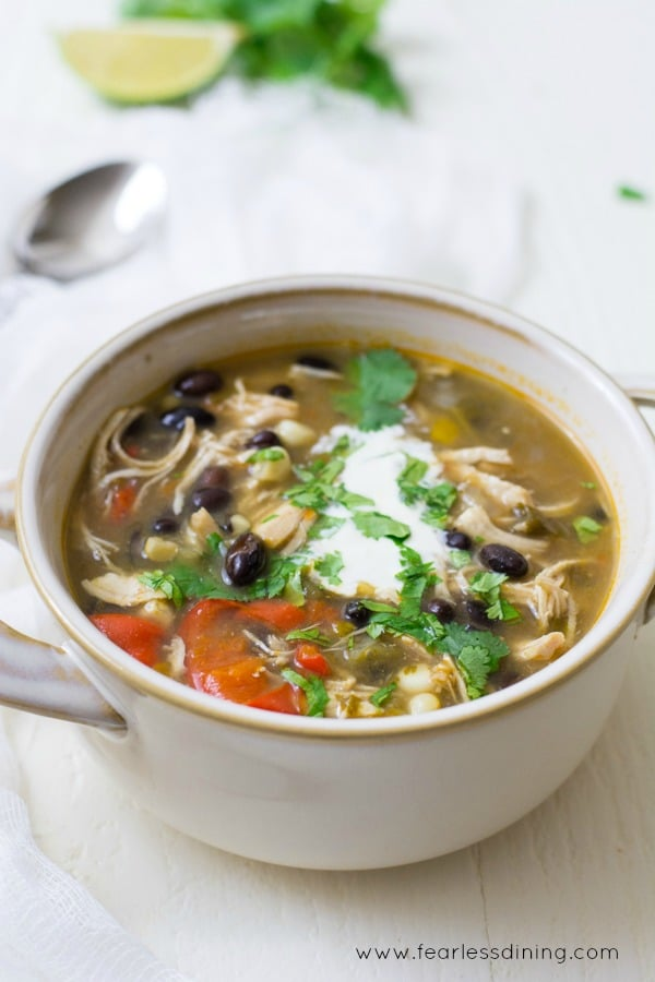 A bowl of taco soup with chicken. The soup is garnished with sour cream and cilantro.