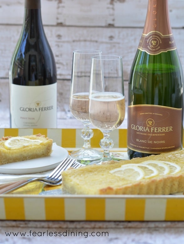 Wine bottles, two filled champagne flutes, and lemon tart are all on a serving tray.