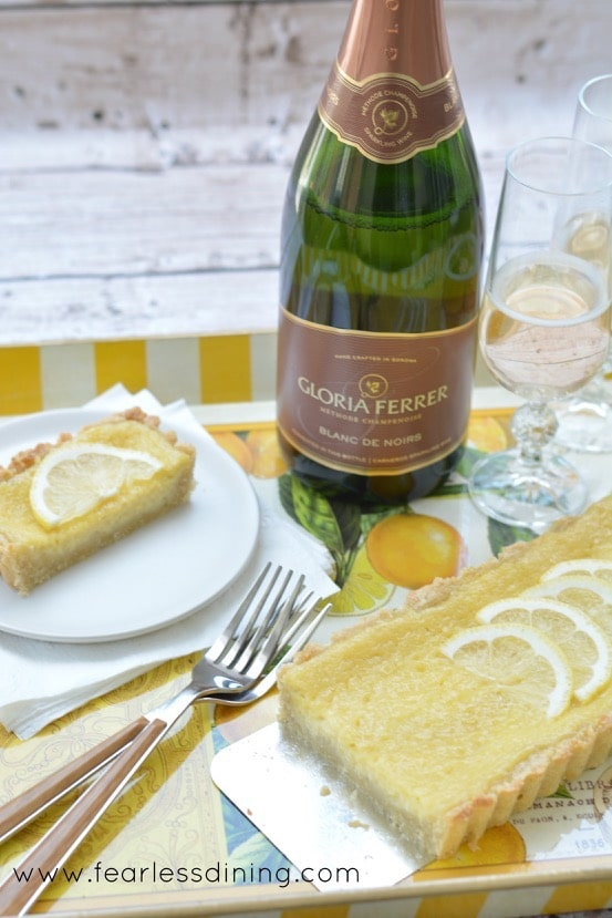 A yellow and white striped serving tray with a lemon tart, forks, sparkling white wine bottle and two champagne glasses.