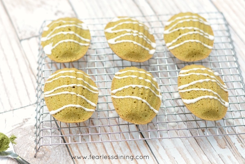 Horizontal picture of six Gluten Free Matcha Madeleines on a cooling rack