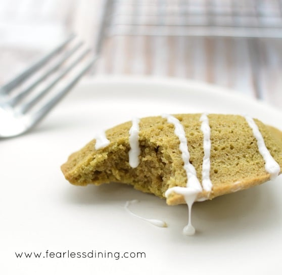 A single Gluten Free Matcha Madeleine on a plate with a bite taken out