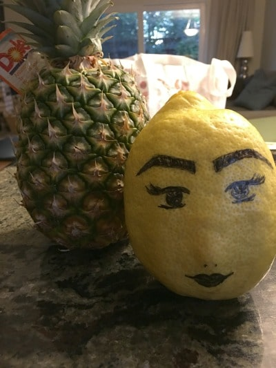A giant lemon next to a pineapple