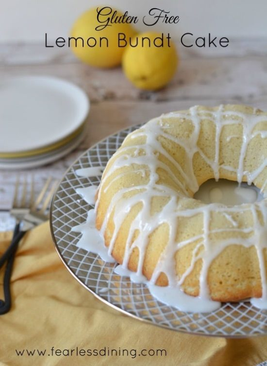 A lemon bundt cake on a cake stand with white icing drizzled on top