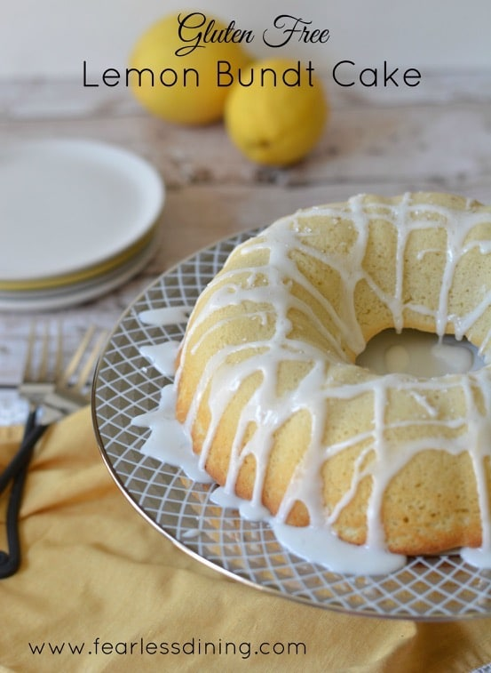 Gluten free lemon bundt cake with a lemonade icing on a cake stand with lemons in the background
