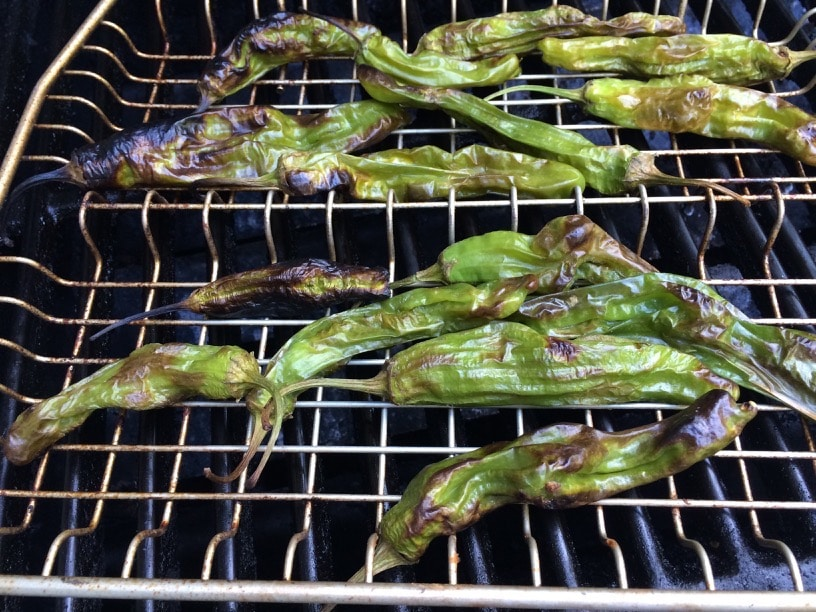 shishito peppers roasting on a grill rack