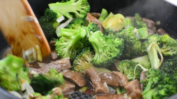 stirring the cooked meat, broccoli and sauce together