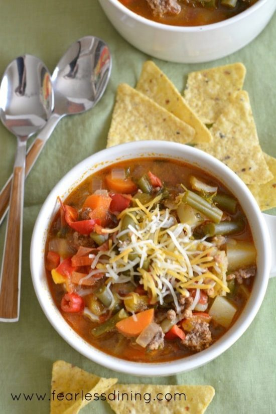 Country Hamburger Vegetable Soup in a large white mug with corn chips around the bowl
