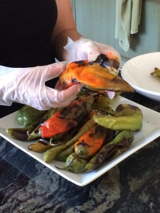 Gloved hands peeling roasted hatch chiles.