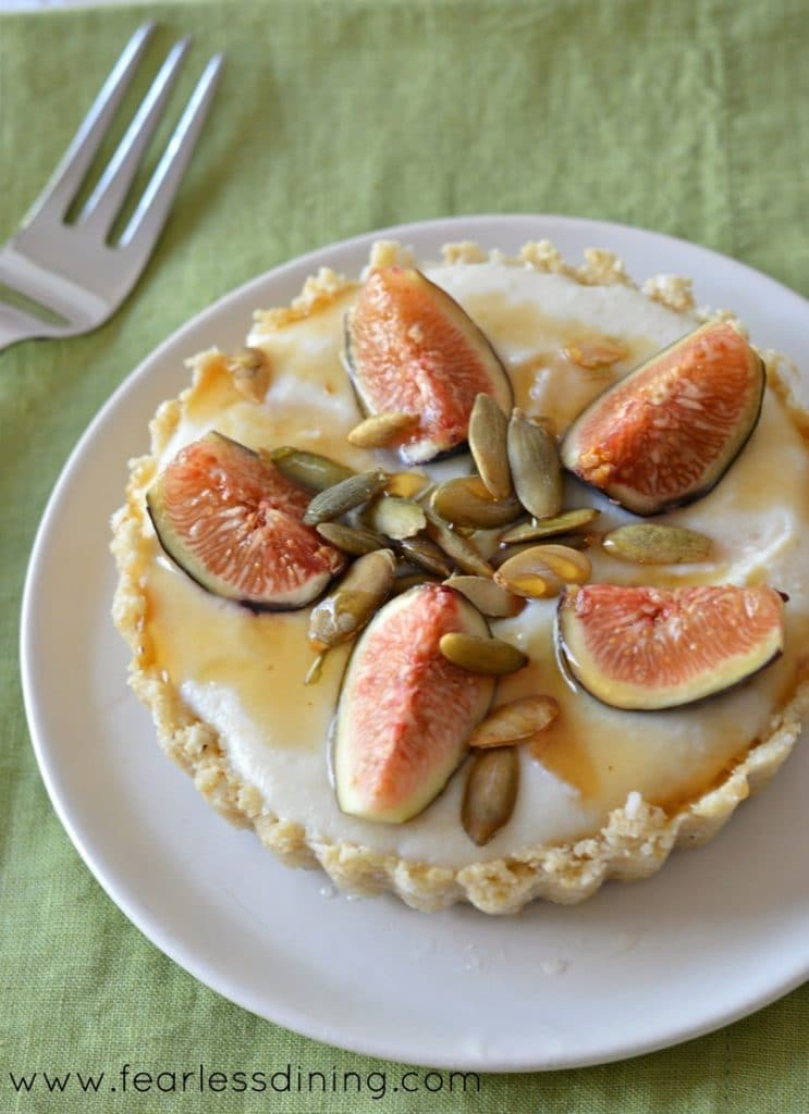 Top view of a raw gluten free fig tart on a plate.