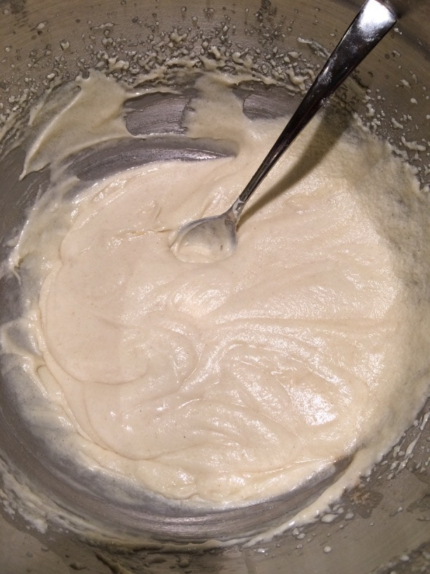 Apple cake batter in a bowl. A spoon is sitting in the batter after stirring.