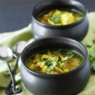black soup crocks filled with comforting tumeric vegetable soup