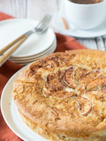 un-sliced gluten free apple cake on a white cake plate