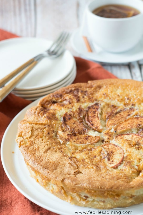 Gluten Free Fool Proof Apple Cake on a plate. A stack of plates and forks are behind the cake
