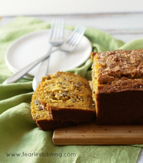 A loaf of Gluten Free Pumpkin bread on a cutting board. The loaf of bread is sliced and you can see walnuts in the bread slices