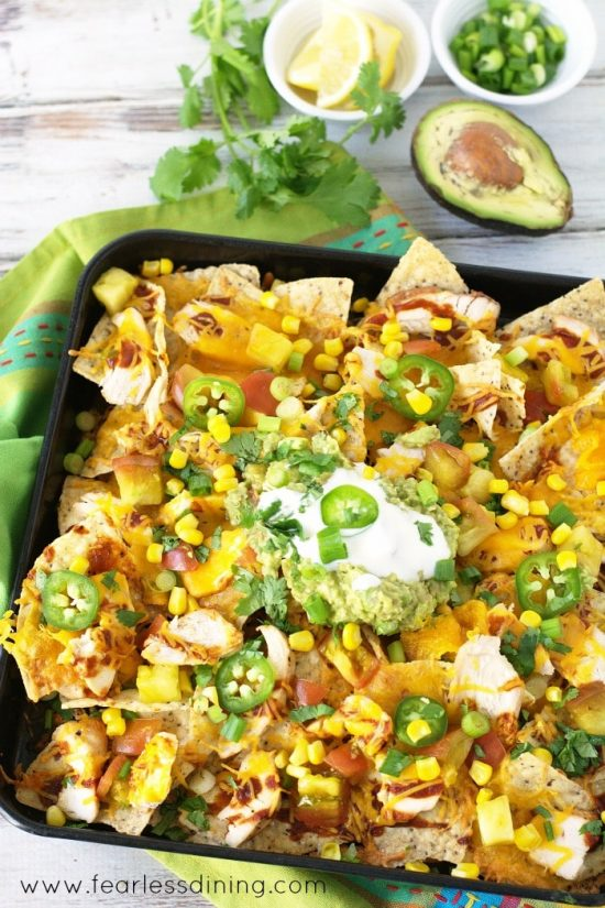 Ultimate Grilled BBQ Chicken Nachos are ready to eat. They are on a tray.