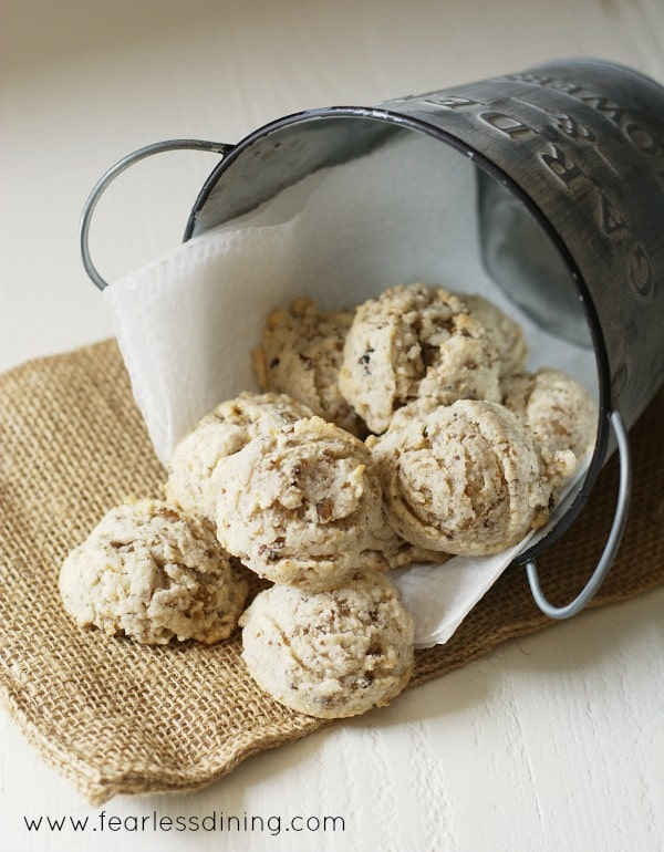 a small metal pail filled with gluten free chestnut cookies. The pail is laying on its side and the cookies are spilling out.