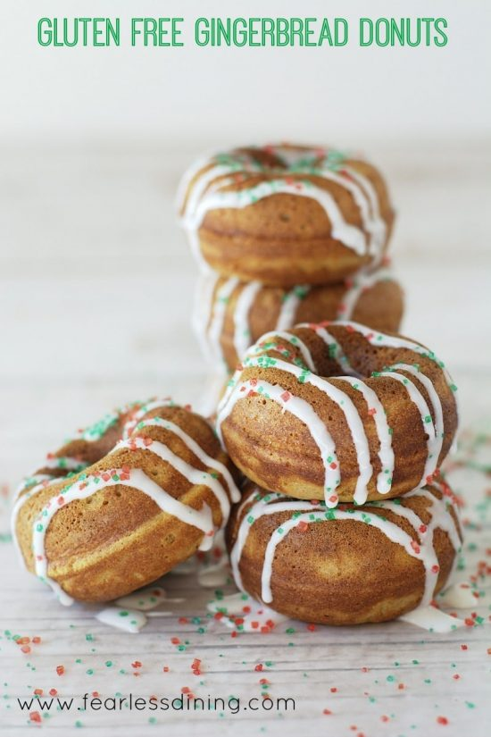 A stack of Gluten Free Gingerbread Donuts with icing and red and green sprinkles