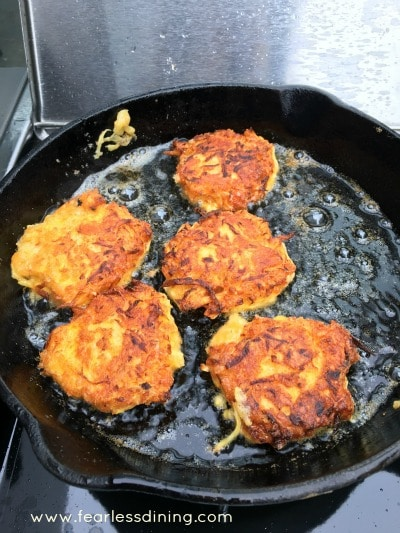 Fritters frying in a cast iron skillet