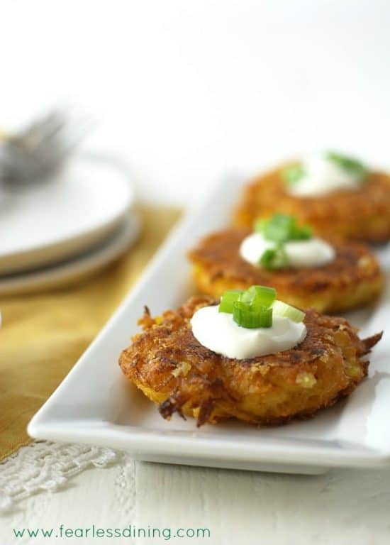 Gluten Free Delicata Squash Cheddar Fritters on a serving tray. The fritters have a dollop of sour cream and fresh scallions on top