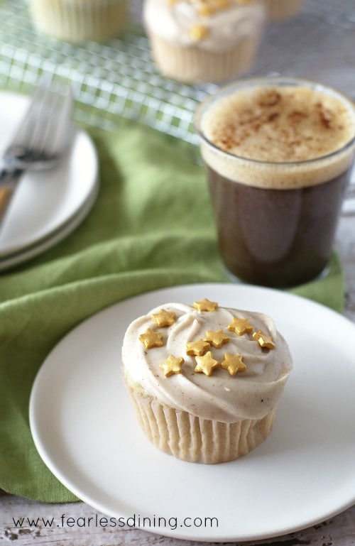 Gluten Free Eggnog Cupcake on a plate with a cup of coffee in the background