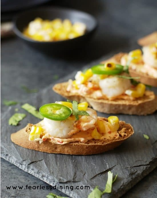 Spicy Shrimp and Roasted Red Pepper Cheese Crostini on a slate serving dish