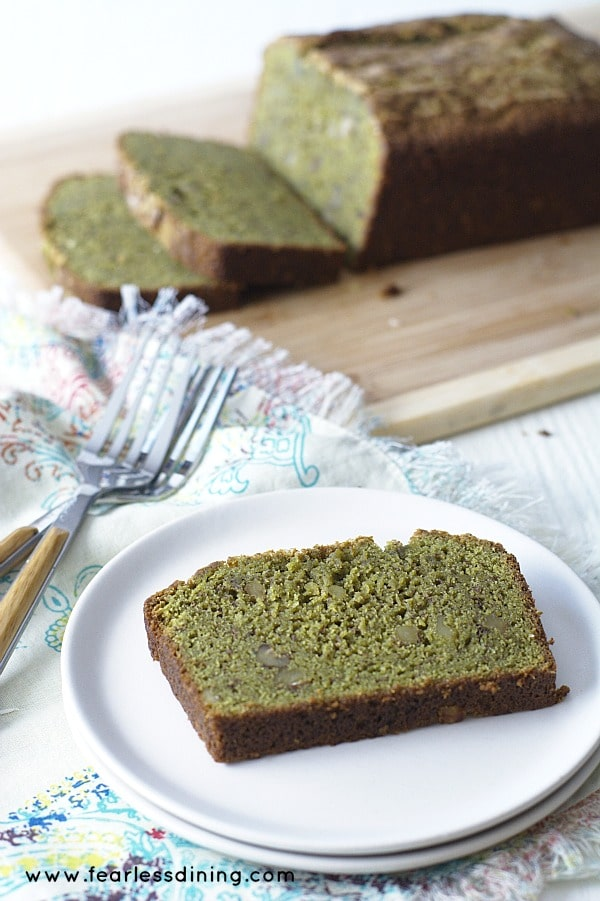 A slice of Gluten Free Matcha Green Tea banana bread on a plate with the bread loaf in the background.