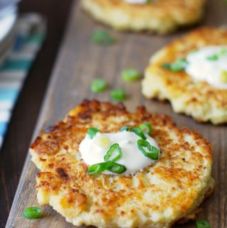 Gluten Free Cauliflower Pancakes made with riced cauliflower, topped with sour cream and scallions