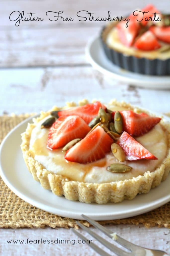 Gluten Free Fresh Strawberry Tarts on white plates. Strawberries and pepitas are on top with a honey drizzle