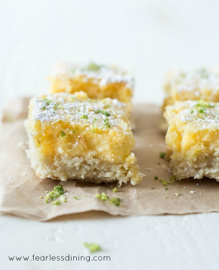 Gluten Free Lime Bars cut in slices and put on a paper bag. Lime zest is sprinkled on top