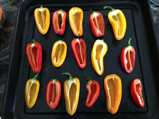 Sweet mini peppers cut in half on a baking tray