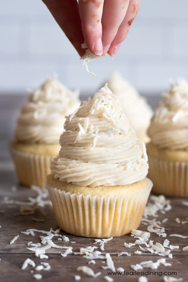 sprinkling shredded coconut over a frosted cupcake