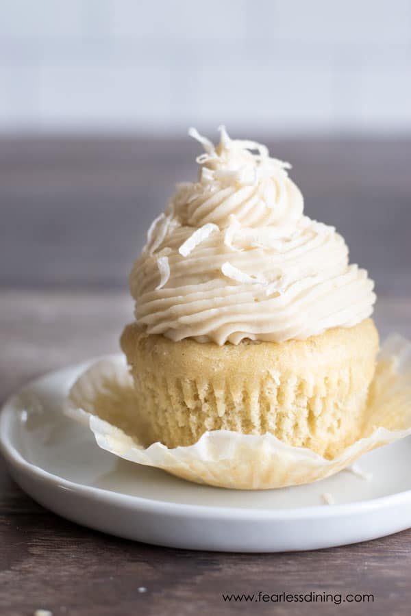 a gluten free lemon curd filled cupcake with the wrapper peeled away