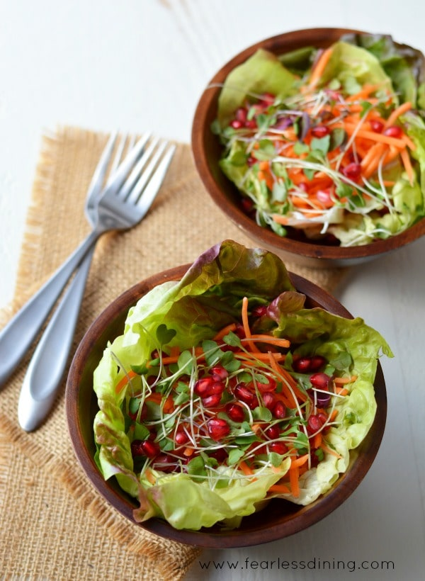 Tossed Salad with Turmeric Vinaigrette in wooden bowls with two forks next to the bowls.