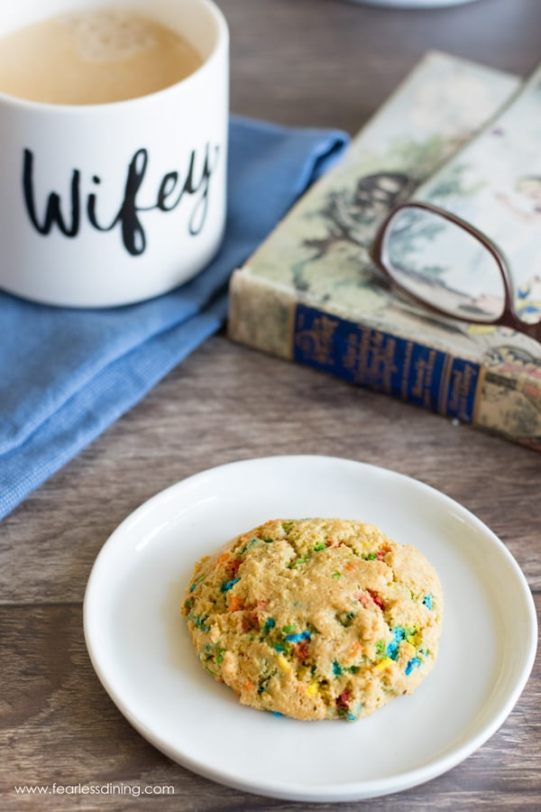 top view of a funfetti cookie on a plate with a cup of coffee and a book next to it.