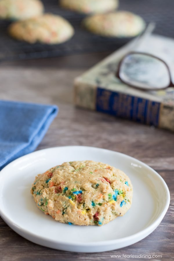 a funfetti rainbow sprinkle cookie on a plate. A book with glasses is next to the plate.