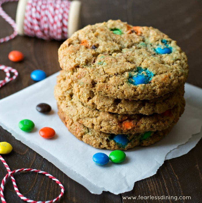 A stack of gluten free monster sized M&M cookies on a napkin. M&Ms are scattered around the cookies