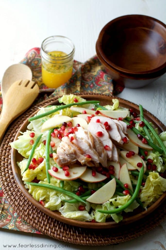 Grilled Chicken Salad with Citrus Vinaigrette in a large wooden bowl. Serving spoons and a jar of dressing are in the background