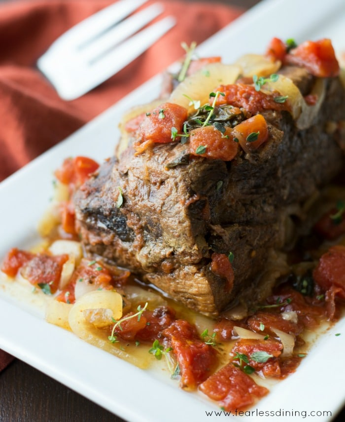 Moist and Juicy 5 Ingredient Crockpot Roast from the side view surrounded by onion and tomatoes.