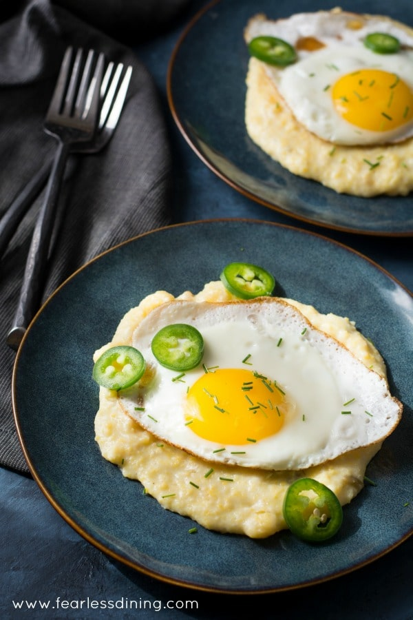 Cheesy Fire Roasted Hatch Chile Grits with Fried Eggs on plates with forks next to the plates