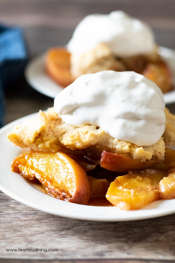 a plate with gluten free peach cobbler on it. There is whipped cream on top of the cobbler.