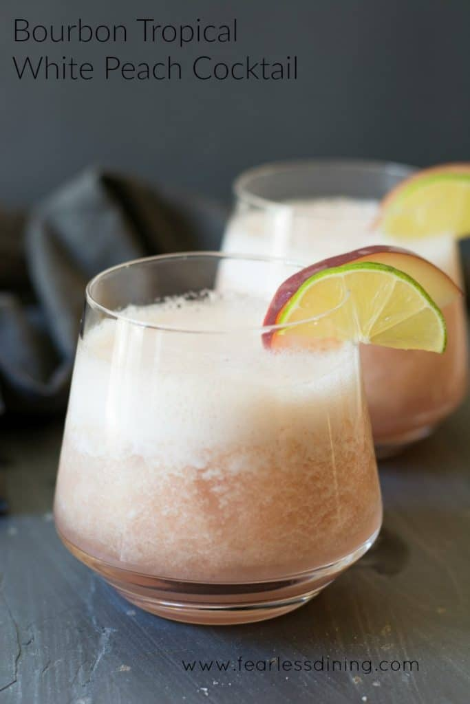 Bourbon Tropical Peach Cocktail in a glass with peach and lime garnish