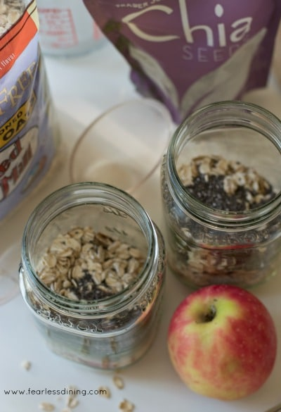 Add oats and chia in mason jars next to an apple