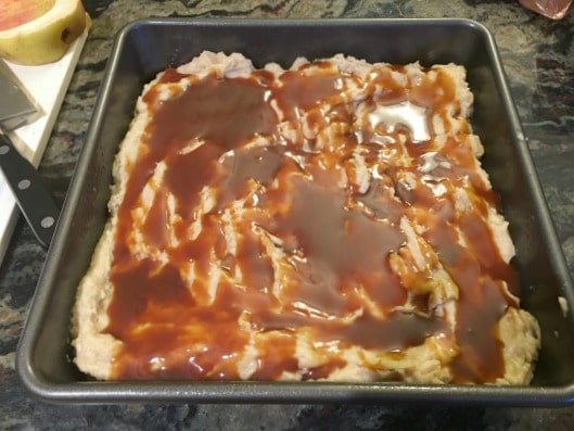 Apple cake batter in a baking pan with caramel on top