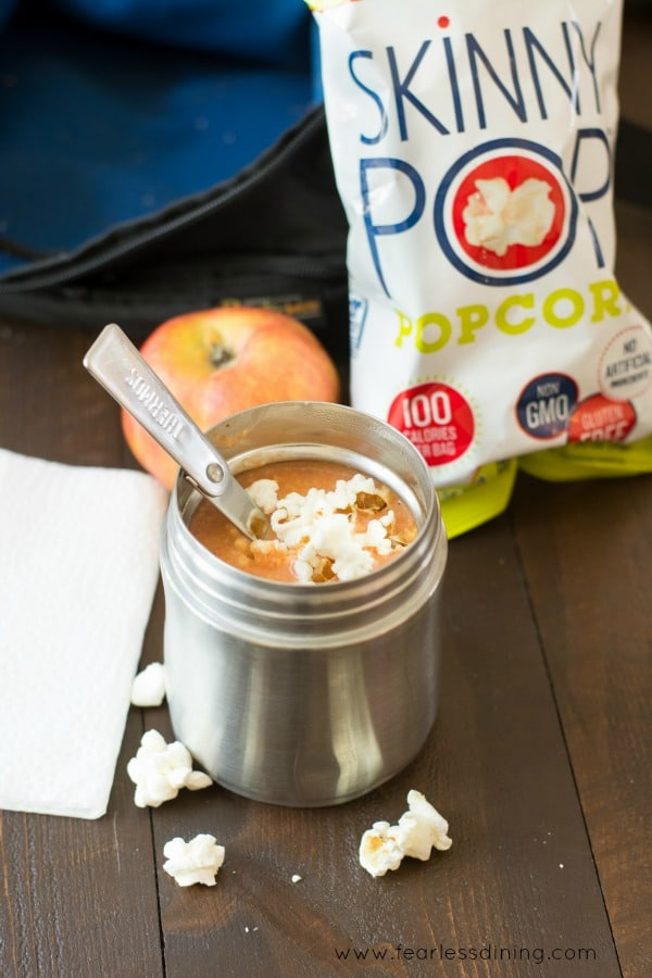Creamy Cheesy Tomato Soup in a thermos with popcorn floating on top. A lunchbox, apple and bag of popcorn are behind the soup