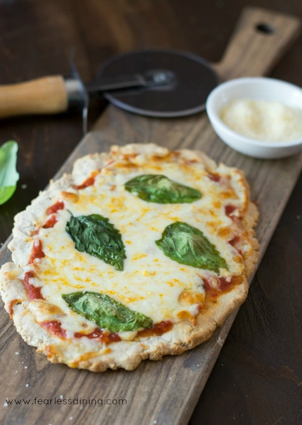 Gluten Free Flatbread Tomato Basil Pizza on a cutting board with a pizza wheel behind the pizza